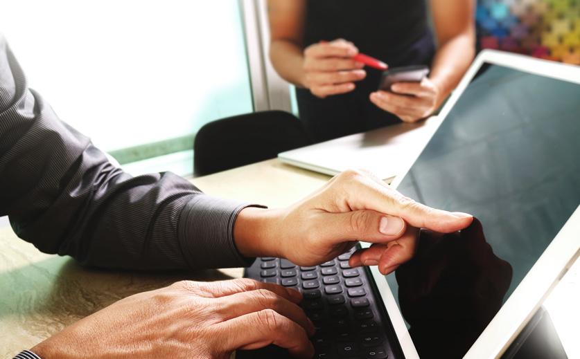 kaksi henkilöä keskustelee verkkosivuista. Toinen osoittaa kannettavan näyttöä ja toinen puhelimen.